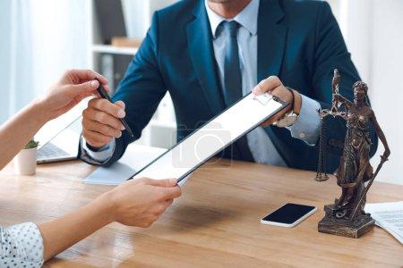 Photo pour Plan recadré de l'avocat donnant presse-papiers et stylo à la jeune femme au bureau - image libre de droit