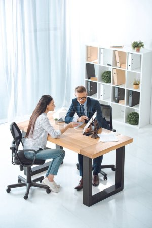 high angle view of lawyer pointing at clipboard and working with female client in office