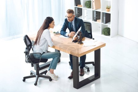 high angle view of lawyer pointing at clipboard and working with young woman in office