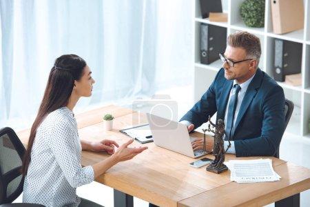 Photo pour Vue d'angle élevé d'avocat travaillant avec le client au bureau - image libre de droit