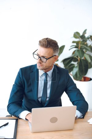 Photo for High angle view of handsome lawyer in eyeglasses using laptop and looking away in office - Royalty Free Image