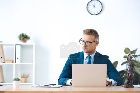 handsome lawyer in eyeglasses using laptop and looking away in office