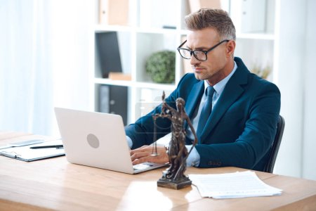 Photo pour Beau avocat dans les lunettes à l'aide d'un ordinateur portable au travail - image libre de droit
