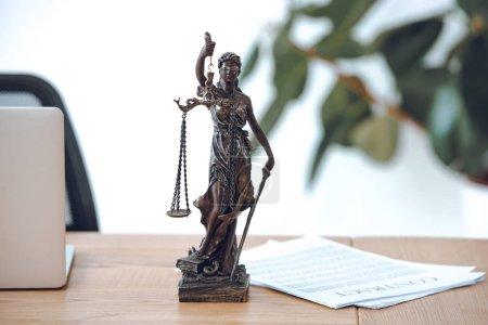 Photo pour Vue rapprochée de la statue de dame de justice, contrat et ordinateur portable sur la table - image libre de droit