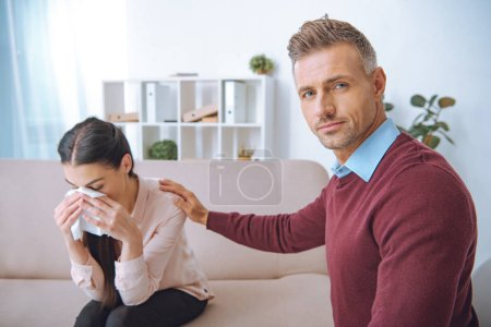 psychotherapist supporting crying patient and looking at camera