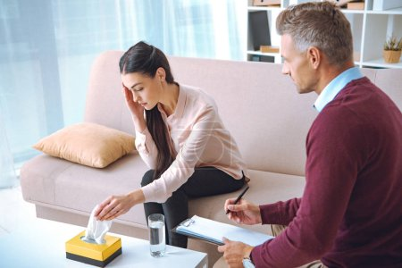 psychotherapist taking notes on clipboard while patient sitting on couch and crying