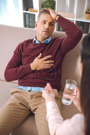 cropped shot of psychotherapist giving glass of water and pill to stressed patient with heartache