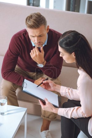 female psychologist pointing at blank clipboard during therapy appointment with male patient
