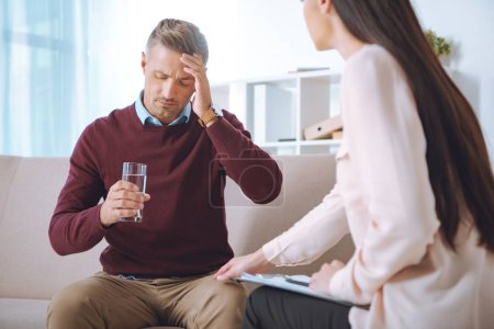 male patient with glass of water having therapy appointment at psychologist office