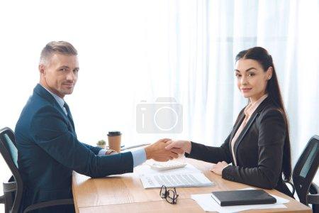 Foto de Socios de negocios dándose la mano en el lugar de trabajo en oficina - Imagen libre de derechos