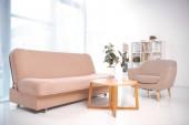 canapé, fauteuil, table basse et étagère avec des dossiers au bureau vide