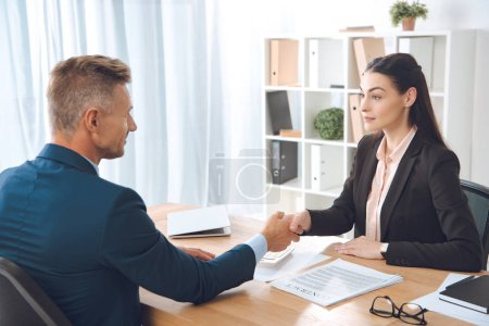 business partners shaking hands at workplace in office