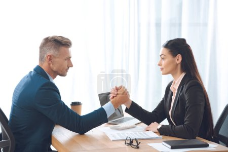 side view of businesspeople arm wrestling at workplace in office