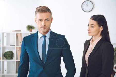 portrait of businesswoman looking at confident colleague in office