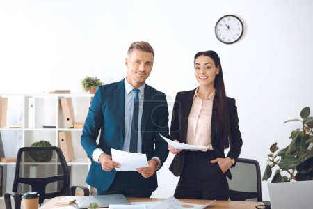 portrait of smiling business colleagues with papers at workplace in office