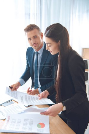 business colleagues doing paperwork at workplace in office