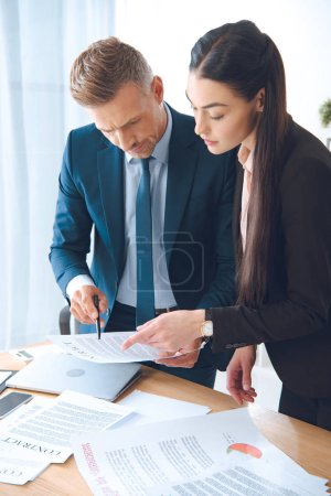 Photo for Focused business colleagues doing paperwork at workplace in office - Royalty Free Image