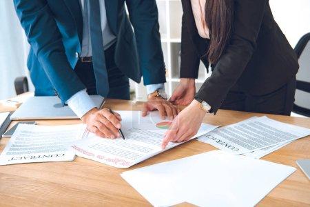 Photo pour Plan recadré de gens d'affaires avec des documents sur le lieu de travail dans le bureau - image libre de droit