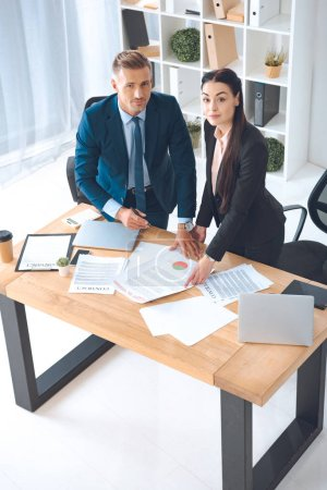 high angle view of business colleagues doing paperwork at workplace in office