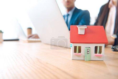 Photo pour Vue partielle des agents d'assurance, au lieu de travail avec le modèle de maison dans le bureau, le concept d'assurance de la maison - image libre de droit