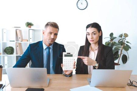 Photo pour Portrait de femme d'affaires, pointant à la calculatrice en main des collègues sur les lieux de travail au bureau - image libre de droit