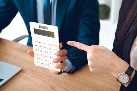 vue partielle de la femme d'affaires, pointant à la calculatrice en main des collègues au travail