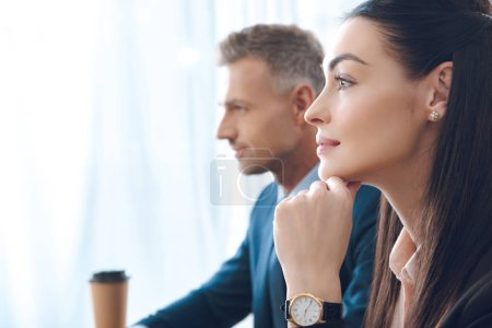 side view of businesspeople looking away in office