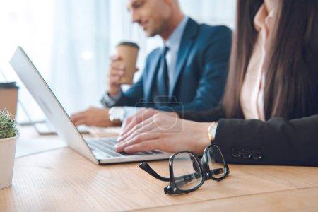 Foto de Vista parcial de empresarios trabajando en computadoras portátiles en el lugar de trabajo en oficina - Imagen libre de derechos