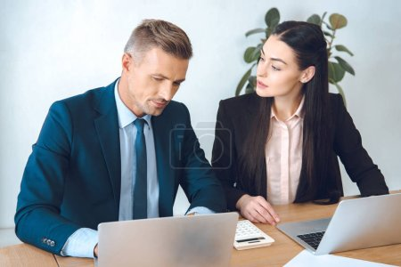 portrait of businesspeople working at workplace with laptop in office