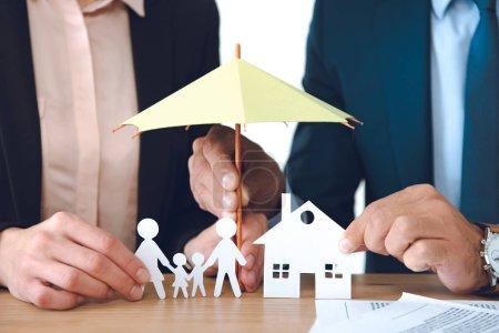 Photo pour Vue partielle des agents d'assurance couvrant les papiers de la famille et la maison des modèles avec parasol sur le lieu de travail - image libre de droit