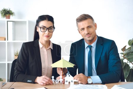 insurance agents covering family and house paper models with umbrella at workplace