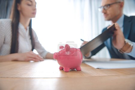 selective focus of insurance agent and client at tabletop with pink piggy bank