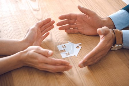 Photo pour Vue partielle des agents d'assurance et des mains féminines avec modèle de maison de papier sur bois sur table, concept d'assurance de la maison - image libre de droit