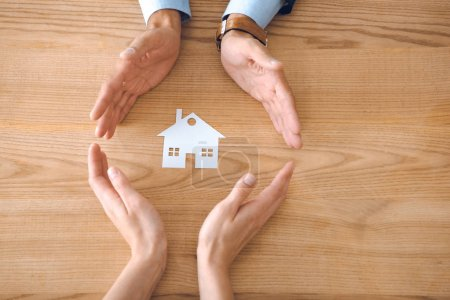 partial view of insurance agents and female hands with paper house model on wooden tabletop, house insurance concept
