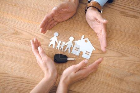 Photo pour Vue partielle des agents d'assurance et des mains féminines avec maison, maquettes en papier famille et clef de voiture sur plateau en bois - image libre de droit