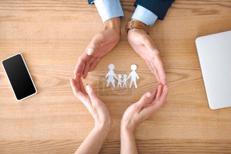 Photo pour Vue partielle des agents d'assurance et des femelles avec modèle familial papier sur table en bois, concept d'assurance familiale - image libre de droit
