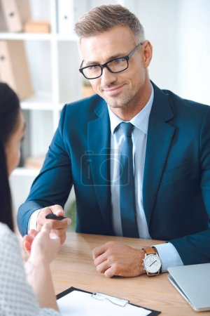 smiling insurance agent giving pen to female client at tabletop in office
