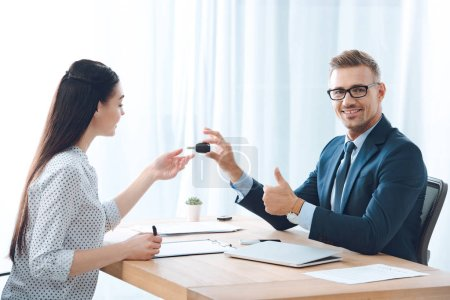 smiling insurance agent giving car key to female client at workplace in office
