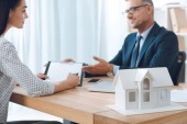 insurance agent in eyeglasses and female client having meeting at workplace with paper house model in office, house insurance concept