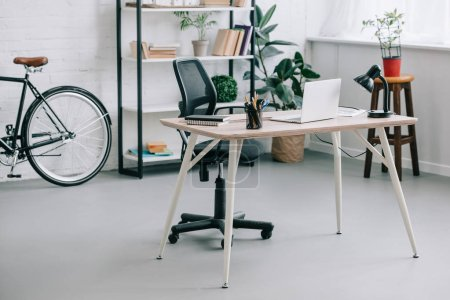 Photo for Interior of modern business office with table, laptop and bike - Royalty Free Image