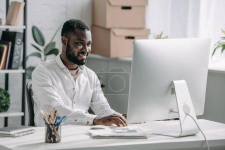 Photo pour Sourire de beau homme d'affaires américain en chemise blanche travaillant à l'ordinateur de bureau - image libre de droit