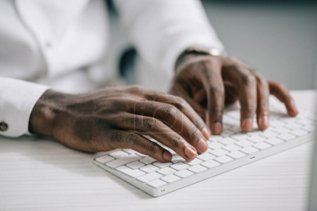 cropped image of african american businessman typing on computer keyboard in office
