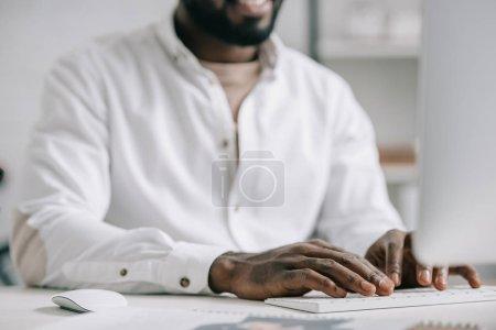 Photo pour Cropped image d'homme d'affaires américain travaillant à l'ordinateur de bureau - image libre de droit