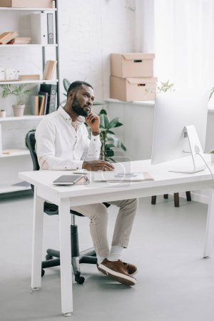 pensive handsome african american businessman sitting at table and looking up in office