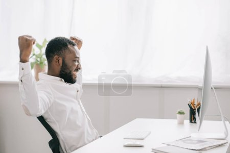 side view of happy african american businessman working at computer in office and showing yes gesture