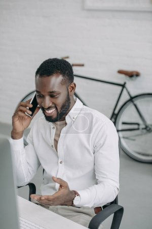 smiling handsome african american businessman talking by smartphone and gesturing in office