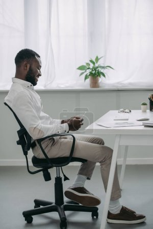 side view of handsome african american businessman sitting at table and using smartphone in office