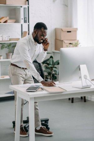 Photo pour Sourire de beau homme d'affaires américain africain parle de smartphone et utilisez l'ordinateur dans le Bureau - image libre de droit