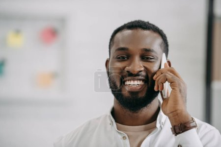 portrait of smiling handsome african american businessman talking by smartphone in office