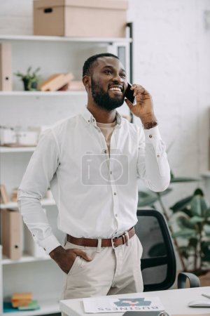 smiling handsome african american businessman talking by smartphone in office and looking up
